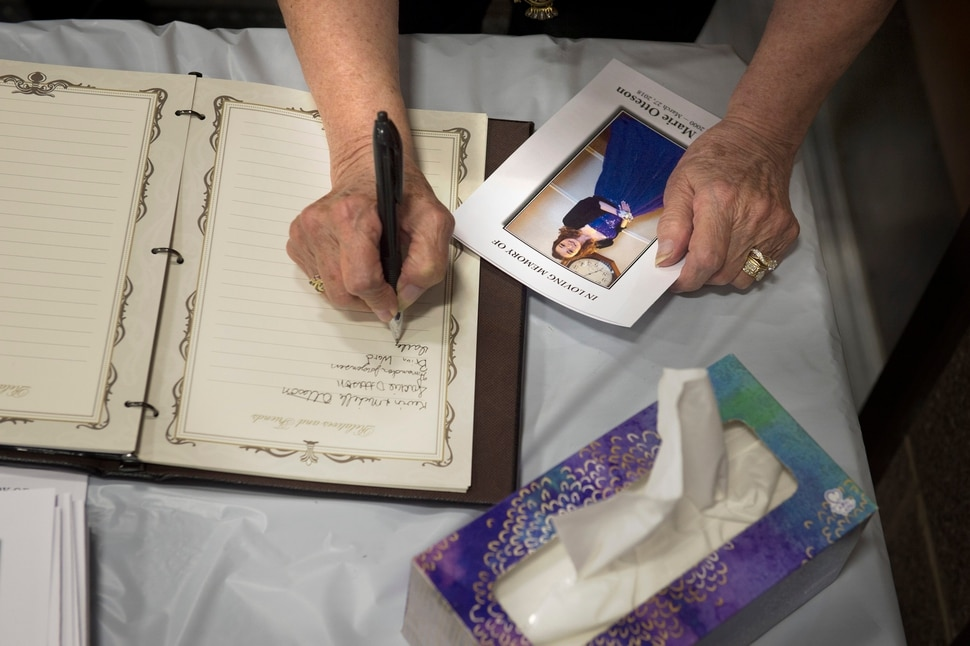 Scott Sommerdorf | The Salt Lake Tribune Friends and family signed the books as they picked up funeral programs at the funeral service for 18-year-old Riley Powell and his 17-year-old girlfriend, Brelynne ÒBreezyÓ Otteson, Saturday, April 6, 2018.