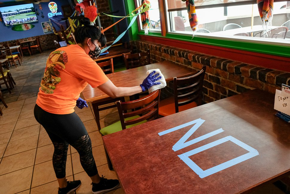 (Francisco Kjolseth | The Salt Lake Tribune) Lucy Walker thoroughly cleans a table at El Chihuahua Mexican restaurant in Holladay as it opens with limited dining on Friday, May 1, 2020.