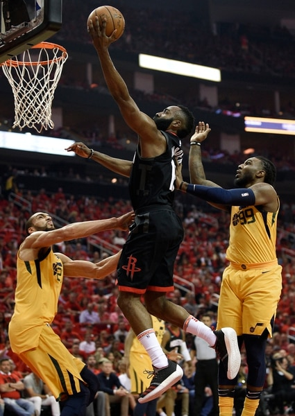 Houston Rockets guard James Harden, center, drives to the basket as Utah Jazz center Rudy Gobert, left, and forward Jae Crowder defend during the first half in Game 1 of an NBA basketball second-round playoff series, Sunday, April 29, 2018, in Houston. (AP Photo/Eric Christian Smith)