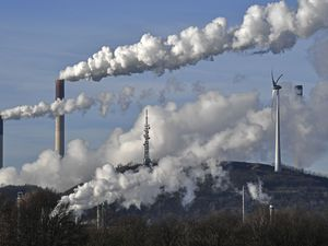 (AP Photo/Martin Meissner)  This Jan. 16, 2020, photo shows a Uniper energy company coal-fired power plant and a BP refinery beside a wind generator in Gelsenkirchen, Germany. The world hit another new record high for heat-trapping carbon dioxide in the atmosphere, despite reduced emissions because of the coronavirus pandemic, scientists announced Thursday, June 4, 2020.