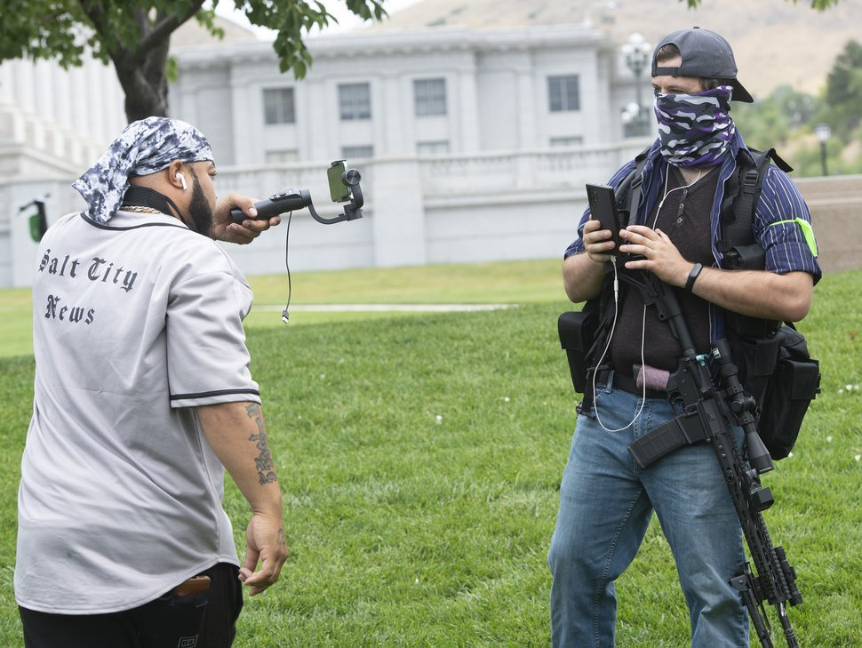 (Rick Egan | The Salt Lake Tribune). Kay Jay from Salt City News films armed counterprotesters on the lawn in front of the State Capitol on Wednesday, July 22, 2020.