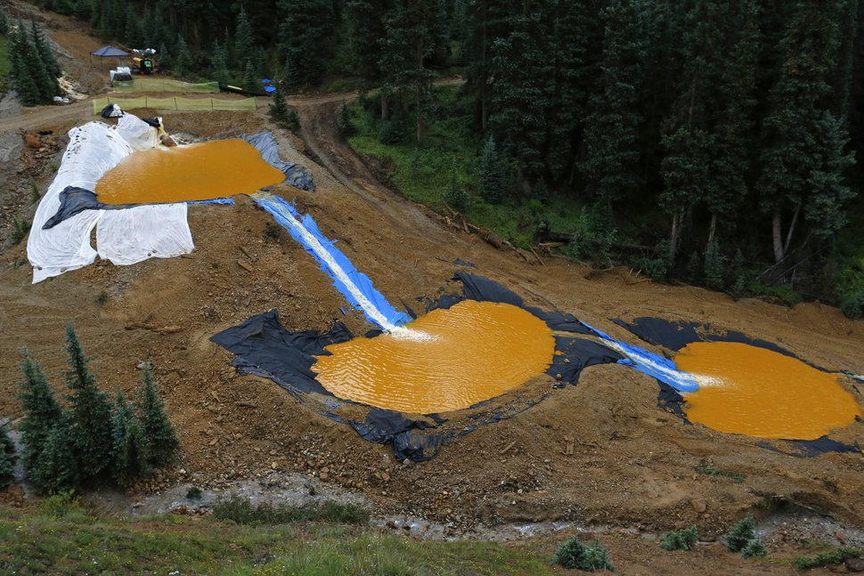 Water flows through a series of retention ponds built to contain and filter out heavy metals and chemicals from the Gold King mine wastewater accident, in the spillway about 1/4 mile downstream from the mine, outside Silverton, Colo., Wednesday, Aug. 12, 2015. The EPA has taken full responsibility for the mine waste spoiling rivers downstream from Silverton, but people who live near the idled and leaking Gold King mine say local authorities and mining companies spent decades spurning federal cleanup help. (AP Photo/Brennan Linsley)