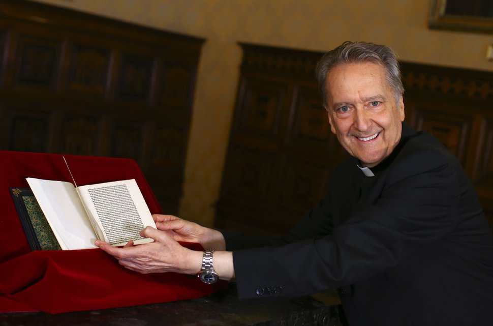 (Tony Gentile/Pool Photo via AP) Prefect of the Vatican Library Bishop Cesare Pasini leafs through an authentic 15th-century copy of a letter written by Christopher Columbus, at the Vatican, Thursday, June 14, 2018. The United States is returning to the Vatican Library a letter written by Christopher Columbus in 1493 announcing his discovery of the New World that was stolen and replaced with a forgery.