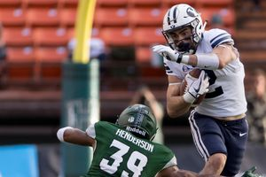 BYU running back Austin Kafentzis (2) attempts to get by Hawaii defensive back Trayvon Henderson (39) in the first quarter of an NCAA college football game, Saturday, Nov. 25, 2017, in Honolulu. (AP Photo/Eugene Tanner)