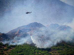 (Trent Nelson | The Salt Lake Tribune) A helicopter makes a drop on the East Canyon Fire as it burns north of East Canyon State Park, on Tuesday, June 8, 2021.