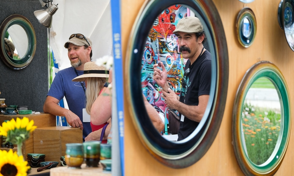 (Francisco Kjolseth | The Salt Lake Tribune) Artists James Diem, left, and Darrell Driver talk to customers while displaying their work side by side during the annual 2019 Utah Arts Festival as it kicks off at Library Square and Washington Square in downtown Salt Lake City, Thursday, June 20, 2019, with visual and performance art of all varieties and food for all ages from June 20-23.