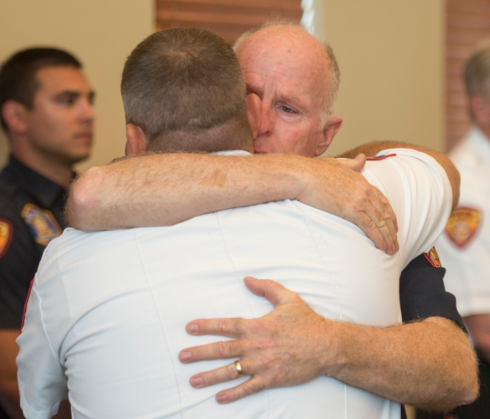 (Rick Egan | The Salt Lake Tribune) Batt. Chief Duane Woolsey with Unified Fire hugs Draper Fire Battalion Chief Bart Vawdrey before a press conference at Draper City Hall about Matt Burchett, 42, who died fighting wildfires in California. Tuesday, Aug. 14, 2018.