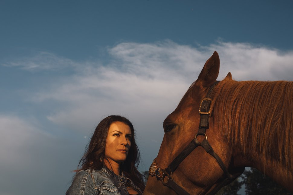 (Amber Bracken | The New York Times) Mellisa Hollingsworth with her horse Tom, near Pine Lake, Canada, July 9, 2020. Hollingsworth and her teammates became case studies in a process that is beginning to realign how brain experts and a handful coaches and athletes are beginning to understand the connection between brain injury and sliding sports.