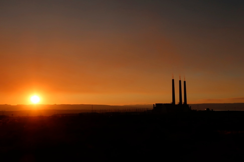 (Felicia Fonseca | AP file photo) The sunsets behind the coal-fired Navajo Generating Station near Page, Ariz., on Aug. 19, 2019. The power plant will close before the year ends, upending the lives of hundreds of mostly Native American workers who mined coal, loaded it and played a part in producing electricity that powered the American Southwest.