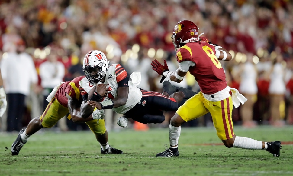 Utah quarterback Tyler Huntley, center, lunges for yardage next to Southern California cornerback Chris Steele (8) during the first half of an NCAA college football game Friday, Sept. 20, 2019, in Los Angeles. (AP Photo/Marcio Jose Sanchez)