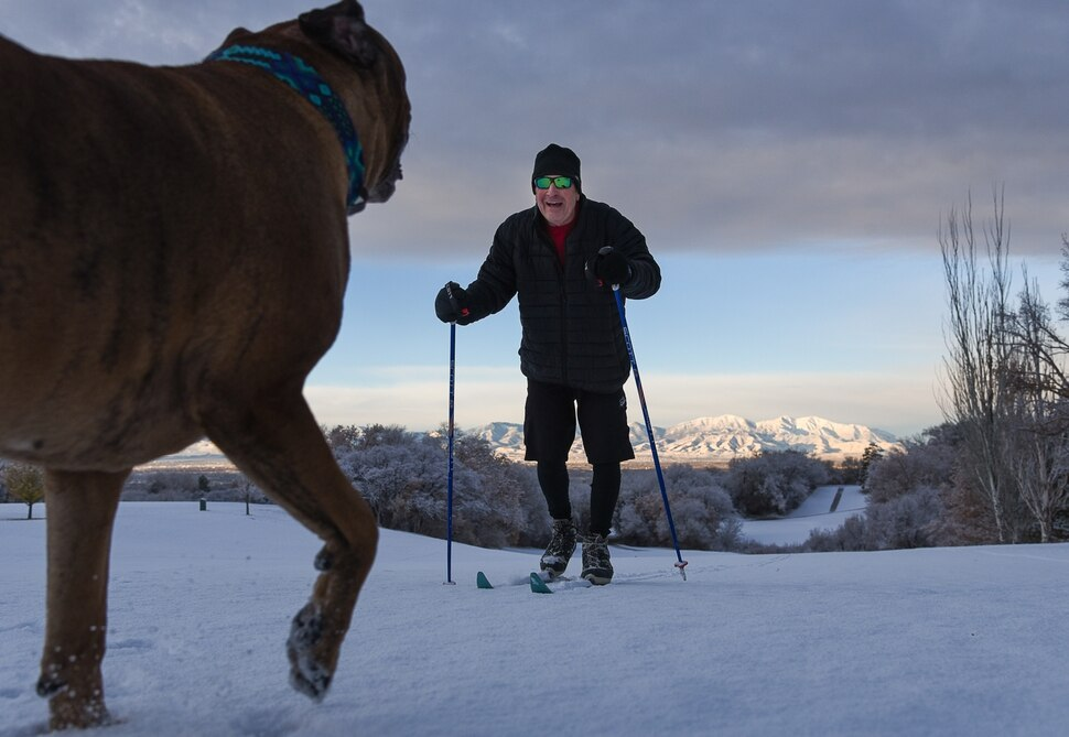 (Francisco Kjolseth | The Salt Lake Tribune) The Oquirrh Mountains are lit up by the early morning sun as recently retired Dr. Rick Anderson makes sure his dog Buddy gets a little exercise at on the slopes of Bonneville Golf Course on Saturday, Dec. 1, 2018. My job is now skiing, said Anderson with plans to head to Alta for some fresh tracks on his own.