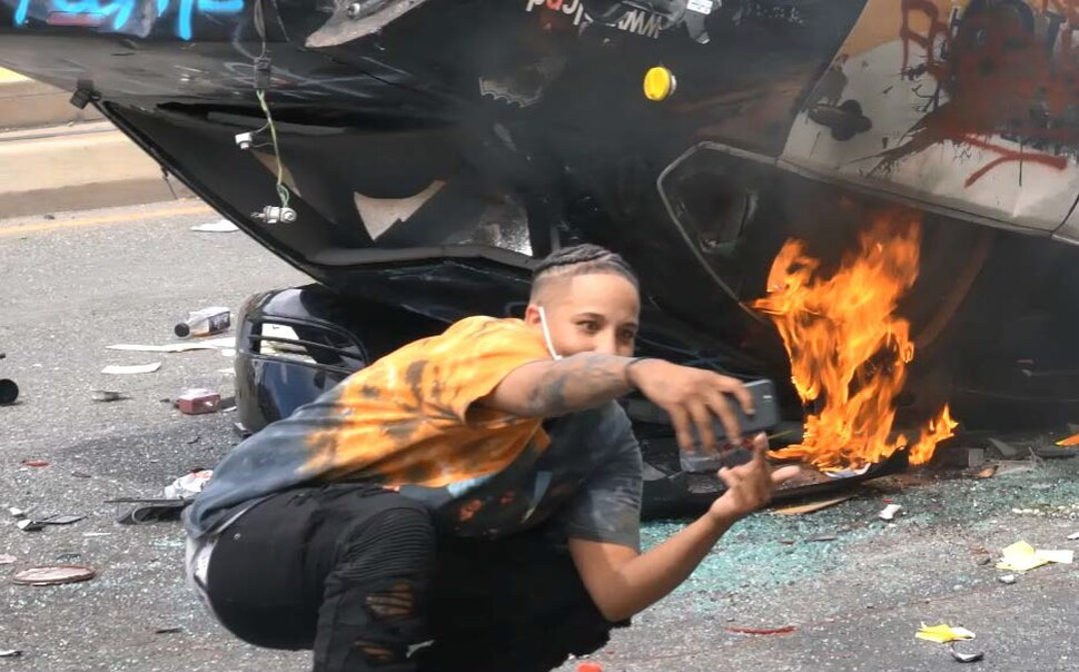 (Photo courtesy of the U.S. Attorney's Office) A person identified as Lateesha Richards of Salt Lake City takes a selfie in front of an overturned and burning Salt Lake City Police Department car on May 30 in Salt Lake City. Richards has been charged with felony arson.