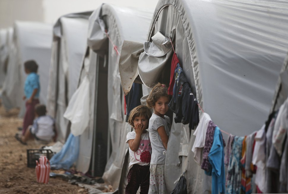 (Lefteris Pitarakis | AP file photo) In this Oct. 11, 2014 file photo, Syrian Kurdish refugee children who fled Kobani with their families stand outside their tent at a refugee camp in Suruc, on the Turkey-Syria border.