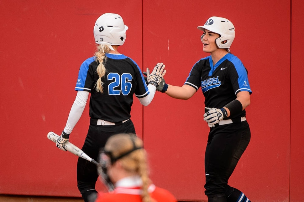 (Trent Nelson | The Salt Lake Tribune) Utah Utes host the BYU Cougars, NCAA softball in Salt Lake City, Wednesday April 18, 2018. BYU outfielder Lexi Tarrow (26) and BYU catcher Libby Sugg (21) celebrate.