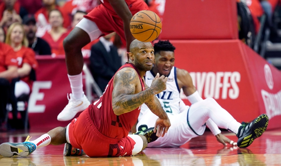 Houston Rockets forward PJ Tucker, left, and Utah Jazz guard Donovan Mitchell, right, scramble for a loose ball during the first half in Game 5 of an NBA basketball playoff series, in Houston, Wednesday, April 24, 2019. (AP Photo/David J. Phillip)