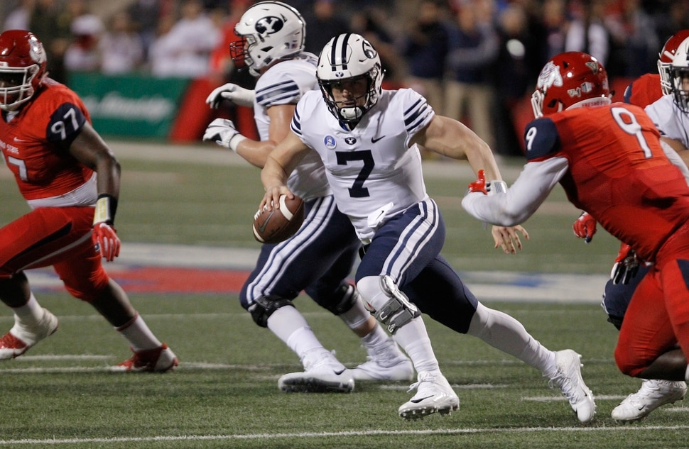 BYU quarterback Beau Hoge tries to avoid Fresno State's Jeffrey Allison, right, during the first half of an NCAA college football game in Fresno, Calif., Saturday, Nov. 4, 2017. (AP Photo/Gary Kazanjian)