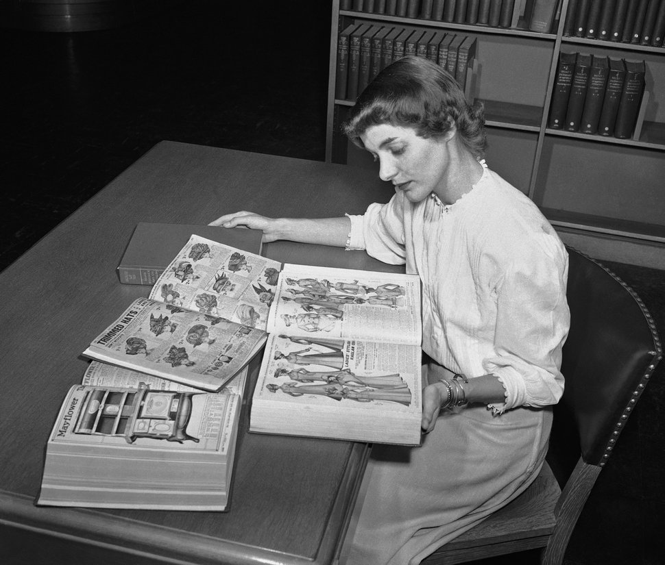 FILE - In an undated file photo, Ruth Parrington, librarian in the art department of the Chicago Public Library, studies early Sears Roebuck catalogs in the library's collection, in Chicago. The catalog Parrington is holding features women's fashion from 1902. Sears, a back-to-school shopping destination for generations of kids and the place newlyweds went to choose appliances, said Tuesday, March 21, 2017, that after years of losing money that there is