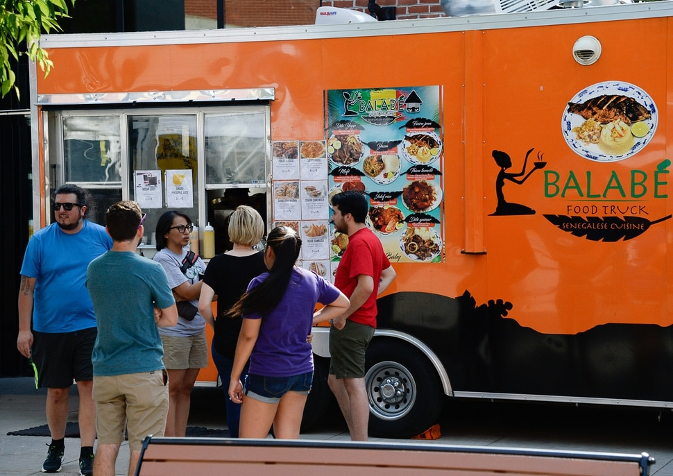 (Francisco Kjolseth | The Salt Lake Tribune) People gather around the Balabe Senegalese food truck during Trolley Square Food Truck Night on Wednesday, July 17, 2019. Three of the vendors for the night, along with four others, will vie for the title of Best New Food Truck on Aug. 3 at the Food Truck and Brewery Battle at The Gateway.