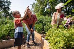 (Francisco Kjolseth | The Salt Lake Tribune) Idris Ahmad, 5, points out sunflowers to Salt Lake City Mayor Erin Mendenhall as they tour the city's newest community garden, at Richmond Park, alongside Jackie Thompson, at right, on Wednesday, Aug. 4, 2021. Thompson dressed up to portray the park's namesake, Mignon Barker Richmond, the first African American woman to graduate from college in Utah.