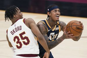 Utah Jazz's Jordan Clarkson, right, drives to the basket against Cleveland Cavaliers' Isaac Okoro during the first half of an NBA basketball game Tuesday, Jan. 12, 2021, in Cleveland. (AP Photo/Tony Dejak)