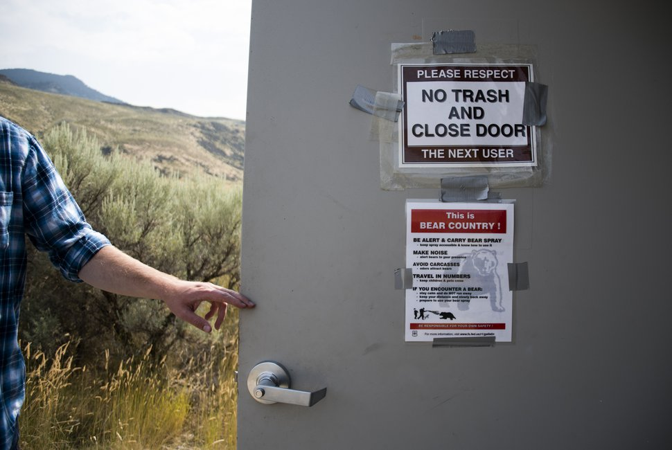(Eli Imadali | Bozeman Daily Chronicle) A user opens the bathroom door at McConnel River Access point in the Gallatin National Forest along the Yellowstone River, just outside Yellowstone National Park. The price of pumping waste out of United States Forest Service bathrooms has increased by over 100 percent over the past five years.