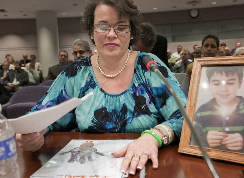 (Jessica Hill | AP Photo) In this Jan. 28, 2013, file photo, Veronique Pozner places her hand next to artwork made by her son Noah before testifying before a hearing of a legislative subcommittee reviewing gun laws at the Legislative Office Building in Hartford, Conn.