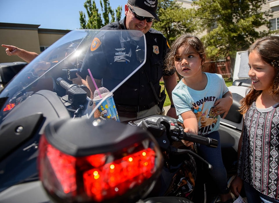 (Trent Nelson | The Salt Lake Tribune) Catalina and Faith Cardenes take a turn on Salt Lake City police officer Michael Blackburn's bike Wednesday June 13, 2018, during an event at a Salt Lake City 7-Eleven store promoting the donation of 7,500 Slurpee coupons by the company for police officers to hand out to children.