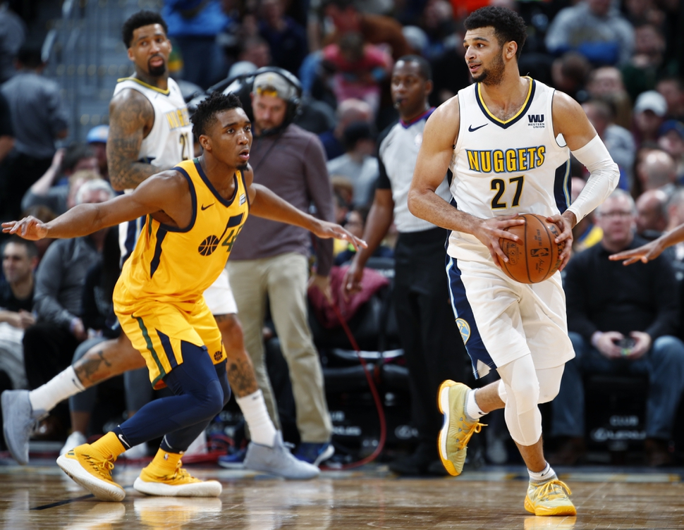 Denver Nuggets guard Jamal Murray, right, looks to pass the ball as Utah Jazz guard Donovan Mitchell defends in the second half of an NBA basketball game Tuesday, Dec. 26, 2017, in Denver. The Nuggets won 107-83. (AP Photo/David Zalubowski)
