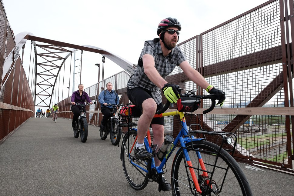 (Francisco Kjolseth | The Salt Lake Tribune) People ride across the new 120-foot arch bridge that connects the north and south sides of the trail between 200 South and North Temple, as part of Salt Lake City's Bike to Work Day.