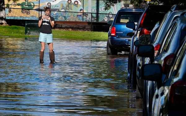 Scott Sommerdorf | The Salt Lake Tribune A Lucy Street resident got out into the flooded street in her boots to make a photo of the flooded street. Northbound Main Line TRAX trains were prevented from leaving the Ballpark TRAX station due to flooding, Wednesday, July 26, 2017.