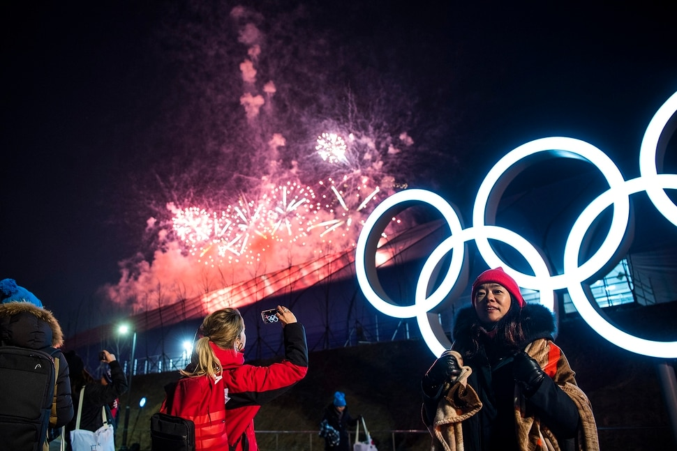 (Chris Detrick | The Salt Lake Tribune) People pose for pictures as fireworks explode during the PyeongChang 2018 Olympic Winter Games Closing Ceremony at Olympic Stadium Sunday, Feb. 25, 2018.