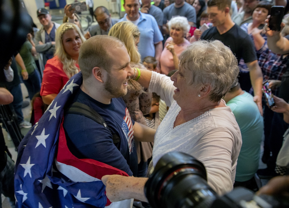 Josh Holt, left, is draped in an America flag by his grandmother, Linda Holt, upon returning to Salt Lake City on Monday, May 28, 2018, as he was freed this weekend after being held in a Venezuelan jail for nearly two years. He returned home to Salt Lake City on Monday night after getting medical care and visiting President Donald Trump in Washington. (AP Photo/Kim Raff)
