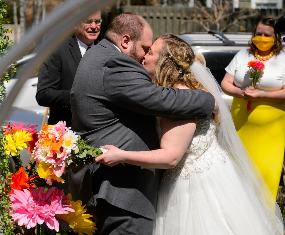 (Trent Nelson | The Salt Lake Tribune) Kadie and Tyler van Roosendaal have their first kiss after being married in a ceremony incorporating social distancing in a Salt Lake City yard on Saturday, April 4, 2020.