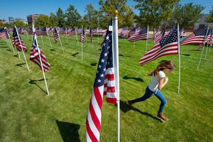 (Francisco Kjolseth  |  Salt Lake Tribune file photo) A child runs among the flags in the Utah Healing Field outside Sandy City Hall on Sept. 11, 2020. For the 20th anniversary of the 9/11 attacks, the Utah Symphony will perform at the ceremony at the field on Saturday, Sept. 11, 2021.