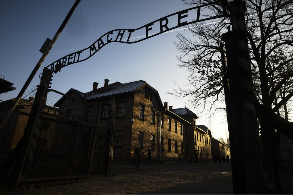 (Markus Schreiber | AP file photo) The sun lights the buildings behind the entrance of the former Nazi death camp of Auschwitz-Birkenau in Poland on Dec. 6, 2019.