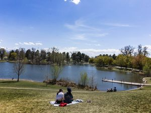 (Rick Egan | The Salt Lake Tribune).  People sit on the grass, as they enjoy the sunny weather, in Liberty Park, on Friday, April 23, 2021.