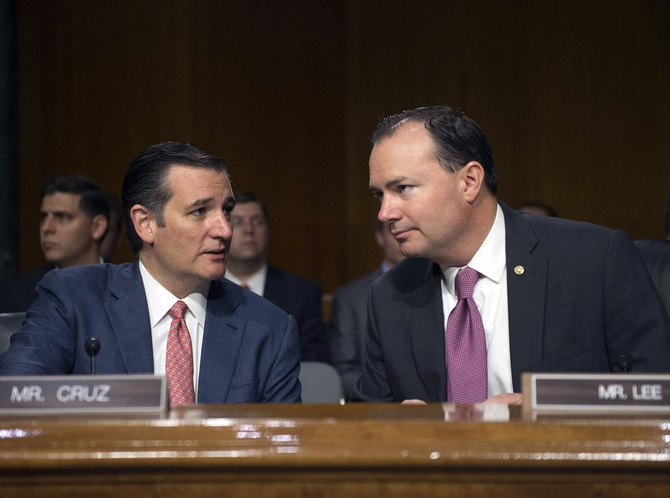 Sen. Ted Cruz, R-Texas, and Sen. Mike Lee, R-Utah, confer before a Senate Judiciary hearing to examine the Obama administration's immigration enforcement policies, in Washington, Tuesday, July 21, 2015. (AP Photo/Molly Riley)