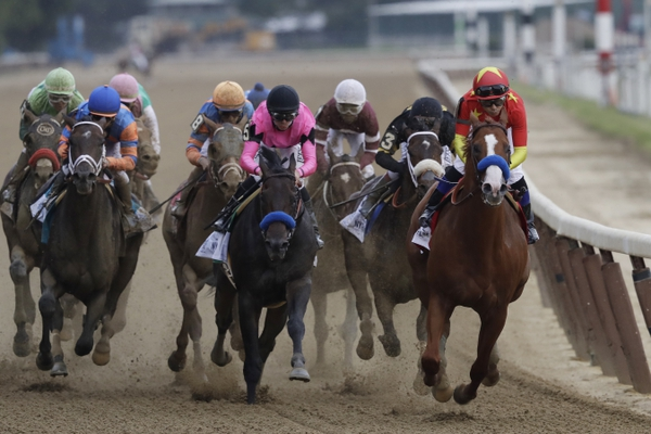 Justify, right, ridden Mike Smith leads the field at the end of the backstretch during the Belmont Stakes horse race, Saturday, June 9, 2018, at Belmont Park in Elmont, N.Y. Justify won the race, to claim horse racing's Triple Crown. (AP Photo/Mark Lennihan)