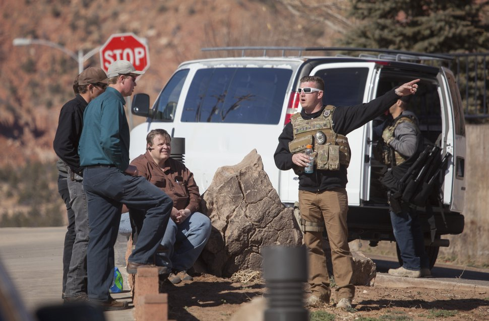 Law enforcement officers investigate in Hildale, Utah, Tuesday, Feb. 23, 2016. Several top leaders from Warren Jeffs' polygamous sect were arrested Tuesday on federal accusations of food stamp fraud and money laundering marking one of the biggest crackdowns on the group in years. (Chris Caldwell /The Spectrum & Daily News via AP) NO SALES; MANDATORY CREDIT