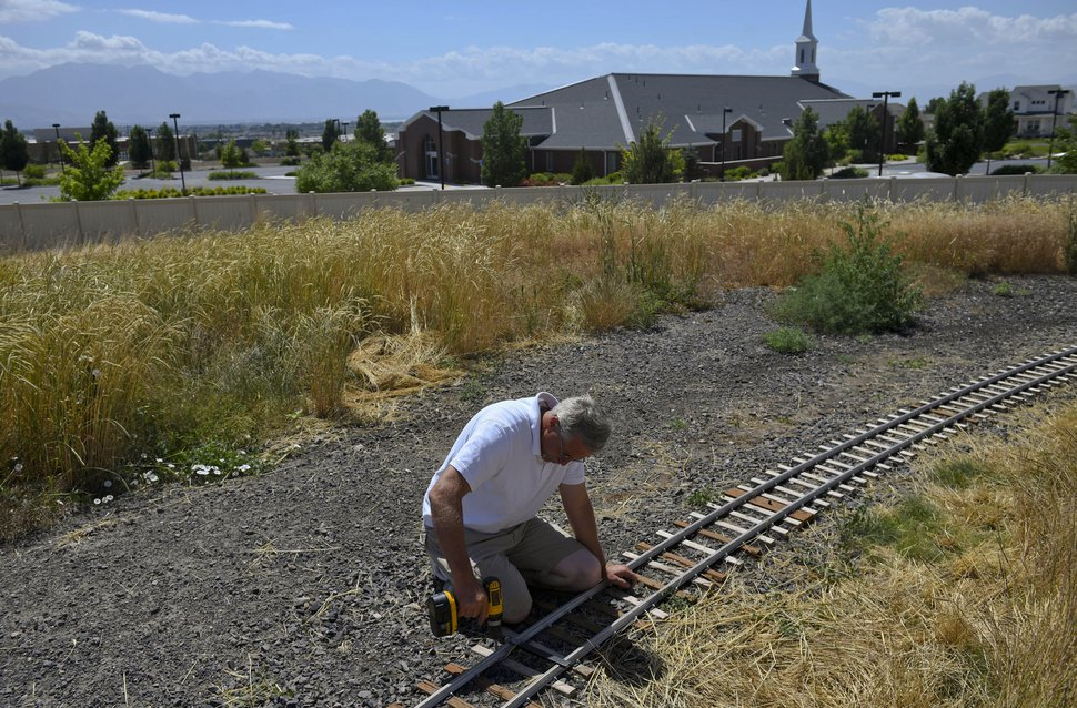 ADVANCE FOR USE WITH WEEKEND EDITIONS JULY 7-8, 2018 AND THEREAFTER In this Saturday, June 16, 2018, photo, Mike Hansen, co-founder of the Utah Live Steamers Railroad Club, corrects a heat kink in a section of track during public train rides held by Utah Live Steamers at Shay Park in Saratoga Springs. Shay Park's name has to do with the history of railroads in the area.