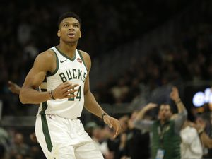 Milwaukee Bucks' Giannis Antetokounmpo reacts after making a 3-pointer during the second half of an NBA basketball game against the Utah Jazz Monday, Nov. 25, 2019, in Milwaukee. (AP Photo/Aaron Gash)