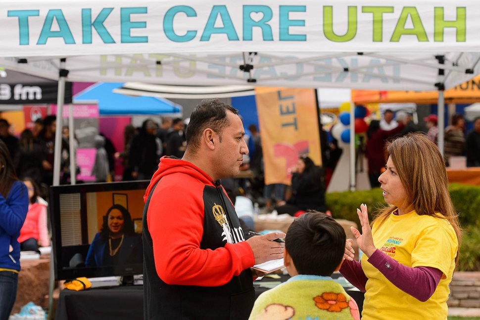 (Trent Nelson | The Salt Lake Tribune) Julie Contreras, one of Take Care Utah's team of enrollment assisters, offers help and advice about applying for health insurance with attendees at the Hispanic Heritage Parade in Salt Lake City, Saturday September 23, 2017.