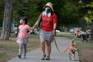 (Francisco Kjolseth  |  The Salt Lake Tribune) Ikue Chambless is joined by her daughter Shiona, 5, as they walk their dog Kaemon at Liberty Park in Salt Lake City while wearing masks due to COVID-19 on Wednesday, July 22, 2020.