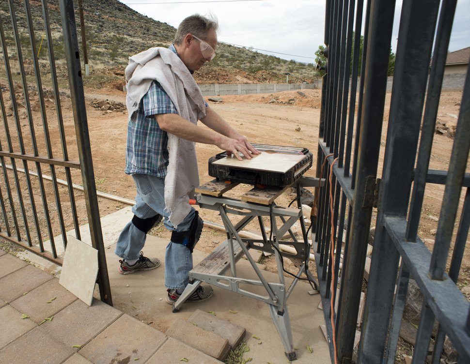 (Rick Egan   The Salt Lake Tribune) Ken Peterson lays tile in his home as he prepares to put his house on the market. Peterson taught music at Dixie State University and was preparing students for their senior recitals when he was terminated in the middle of the semester. Friday, April 6, 2018.