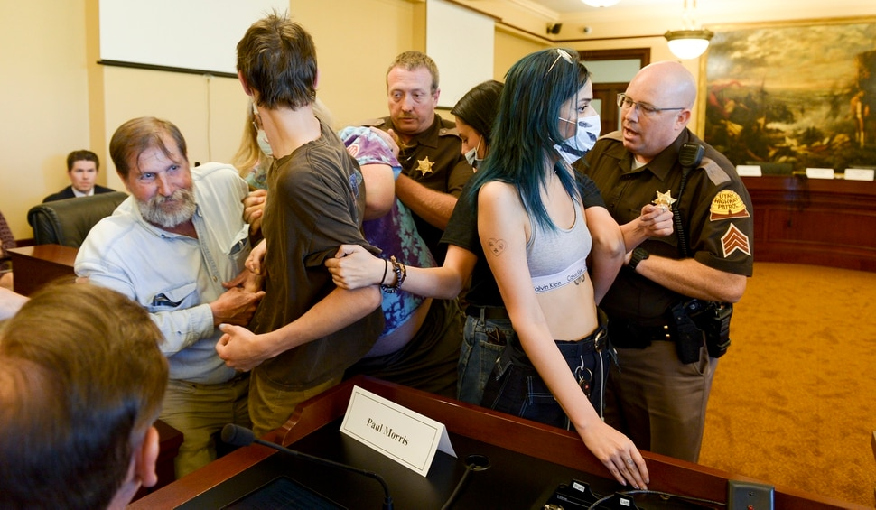 (Leah Hogsten | The Salt Lake Tribune) Opponents of the proposed inland port are escorted out of the Utah Inland Port Authority Board meeting by Utah Highway Patrol officers at the Capitol, June 5, 2019. The Inland Port Authority Board had to cancel its meeting last month after a group of protesters took over the meeting.