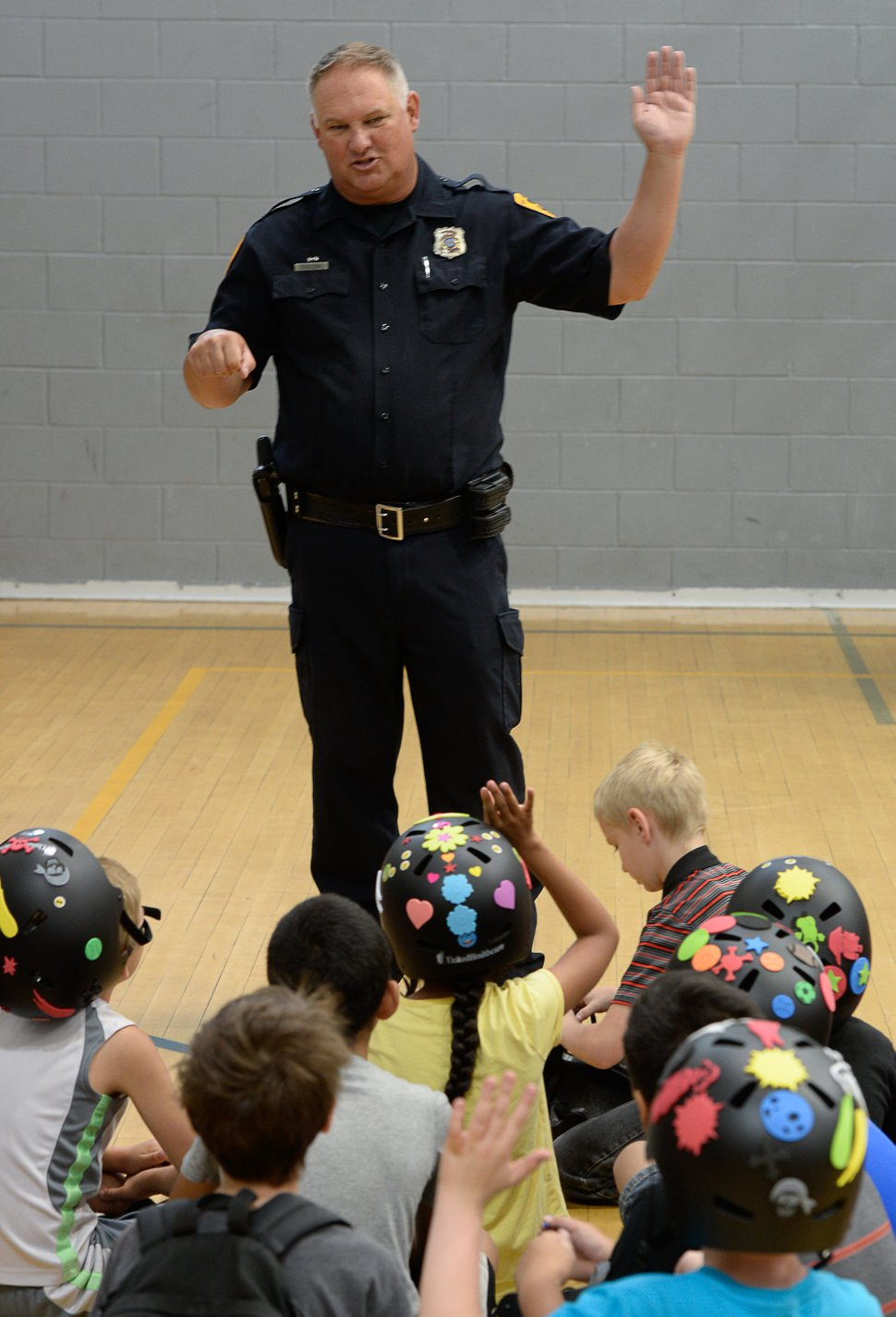 (Francisco Kjolseth | Tribune file photo) Detective Greg Wilking shows kids the proper way of signaling their turns while on the bike as more than 50 Salt Lake City-area kids received a new bicycle helmet at the Capitol West Boys & Girls Club on Tuesday, July 31, 2018. Wilking is spokesman for the Salt Lake City Police Department and responded to questions about missing evidence in cold cases.