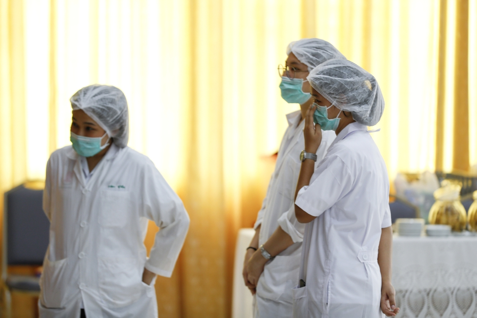 Hospital workers watch a press conference at their hospital where rescued boys are tended to, in Chiang Rai province, northern Thailand, Tuesday, July 10, 2018. A Thai public health official said Tuesday the eight boys rescued from a flooded cave in northern Thailand are in high spirits and have strong immune systems because they are soccer players. (AP Photo/Vincent Thian)