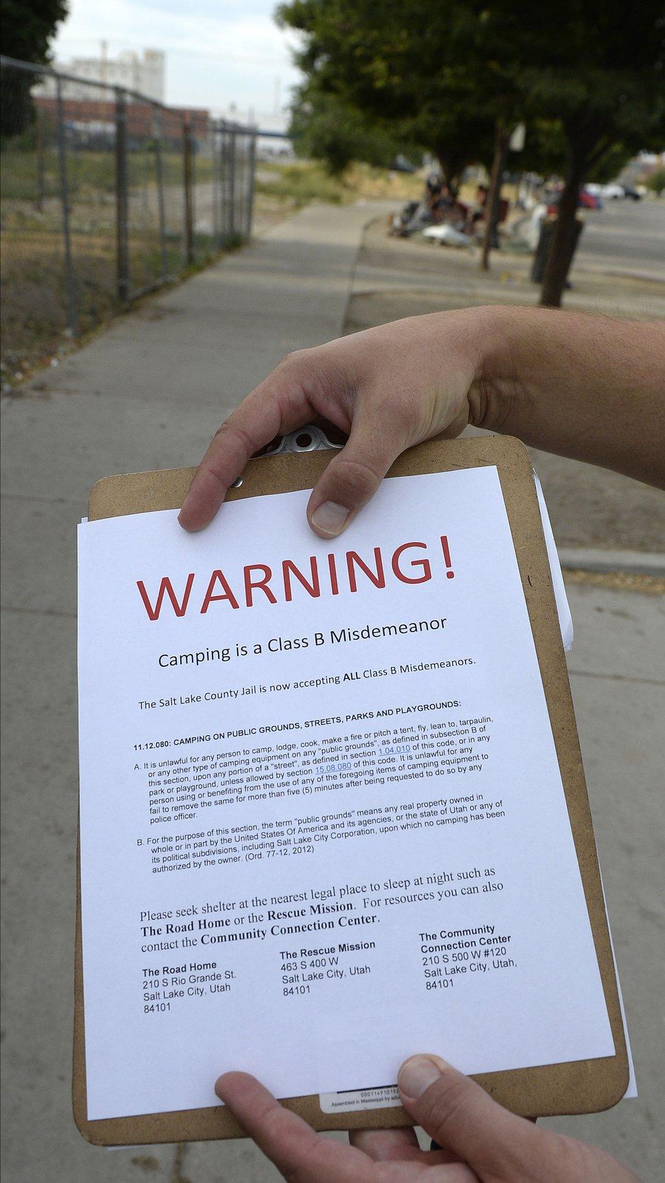 Al Hartmann | The Salt Lake Tribune Salt Lake City police Sgt. Sam Wolf shows a warning notice that says camping on the sidewalks in Salt Lake City is a class B misdemeanor.