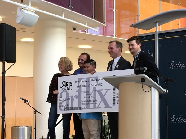 (Photo courtesy of SLCTV) Brandon Montes, center, an 11-year-old student at Whittier Elementary, is joined onstage by (from left) Salt Lake City Mayor Jackie Biskupski, Salt Lake County Council Member Max Burdick, Salt Lake County Mayor Ben McAdams, and Salt Lake City Council Member Chris Wharton, and is presented with a symbolic ticket as the first recipient of the Arts for All program.