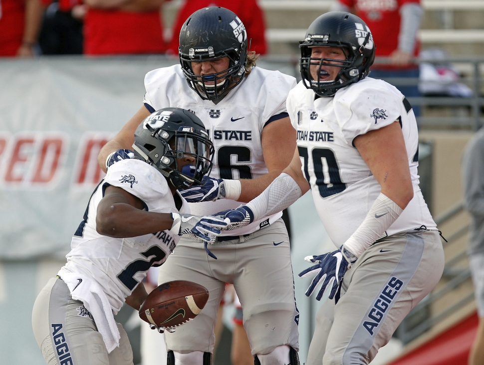 Utah State running back LaJuan Hunt, left, celebrates with teammates Rob Castaneda, right, and Roman Andrus after scoring a touchdown during the first half of an NCAA college football game against New Mexico in Albuquerque, N.M., Saturday, Nov. 4, 2017. (AP Photo/Andres Leighton)